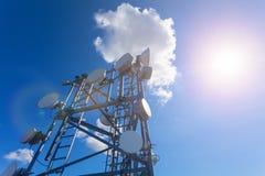 Telekomunikaci wierza z mikrofalą, radiowymi antenami i antenami satelitarnymi z cieniami na dachu przeciw, niebieskiemu niebu i  Obraz Stock