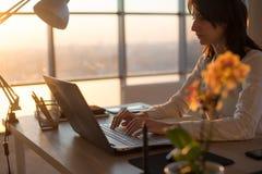 Telelavoratore femminile che manda un sms facendo uso del computer portatile e di Internet, lavoranti online Free lance che scriv Fotografia Stock