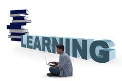telelearning概念的年轻人与膝上型计算机和书 库存图片