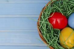 Telemóvel amarelo A cesta da Páscoa encheu-se com os ovos coloridos em um fundo de madeira azul com espaço da cópia para felicita imagens de stock royalty free