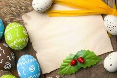 Telemóvel amarelo Ovos da páscoa pintados com pedaço de papel para felicitações em um fundo de madeira natural fotografia de stock royalty free