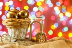 Telemóvel amarelo Ovos dourados em um carro da bicicleta Ovo Easter feliz Fotografia de Stock Royalty Free