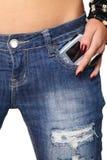 Telemóvel moderno que fura fora do calças de brim imagem de stock