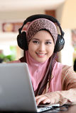 Telemarketing. Young pretty Asian muslim woman in head scarf listens to audio with headphone while working on laptop in cafe Stock Image