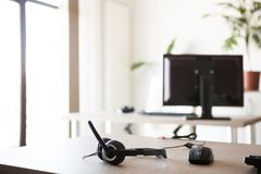 Telemarketing headset lying on the table. Close up image. Modern office interior Stock Photos