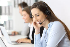 Telemarketing operator working at office. Telemarketing operator talking working at office with other workers in the background Royalty Free Stock Photos
