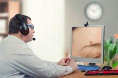 Telemedicine dermatologist examines mole above eyebrow Royalty Free Stock Image