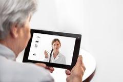 Telemedicine eller Telehealth med en doktor och en hög kvinna med royaltyfri foto