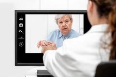 Telemedicine och åldringen att bry sig med en hög kvinna och en doktor I arkivfoto