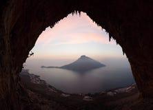 Силуэт альпиниста утеса на скале против рисуночного взгляда острова Telendos на заходе солнца Стоковые Фотографии RF