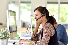 Teleoperator in front of desktop. Portrait of smiling customer service operator Stock Photos