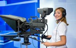 Teleoperator at TV studio. A female cameraman at a studio smiles into camera Royalty Free Stock Photos