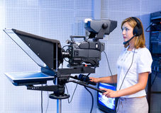 Teleoperator at TV studio. A female cameraman at a studio during live broadcasting Royalty Free Stock Images
