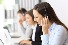 Teleoperator working at call center. Happy teleoperator working at call center with other employees in the background stock image