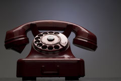 Telephone. An old red telephone against gray background Stock Image