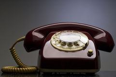Telephone. An old red telephone against gray background Royalty Free Stock Photography