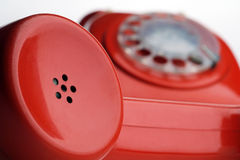 Telephone. A red rotary dial telephone off the hook - focus on the receiver Stock Photo