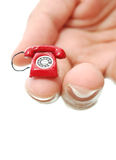 Telephone. Miniature red telephone held by fingers of a hand Royalty Free Stock Photos
