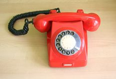 Telephone. One old, red telephone on a desk Royalty Free Stock Images