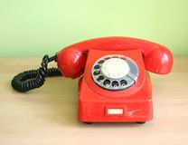 Telephone. One old, red telephone on a desk Stock Photography
