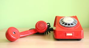 Telephone. One old, red telephone on a desk Royalty Free Stock Photography