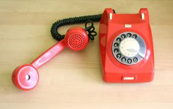 Telephone. One old, red telephone on a desk stock photo