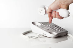 Telephone. Image of a telephone on a white background with a hand in the shot making a call Stock Image