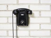 Telephone. Black bakelite telephone on a brick wall Royalty Free Stock Photos