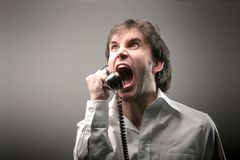 Telephone 488. A man with crazy expression screaming on the telephone Royalty Free Stock Image