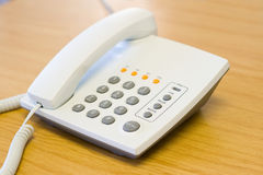 Telephone. A white modern telephone on a wooden table Royalty Free Stock Photos