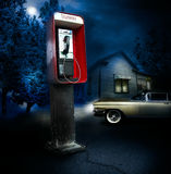 Telephone. A red telephone booth in an unwelcome frightening area at night.  A large older car sits in the background with lights on while driver prepares to Stock Image