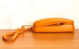 Telephone. The orange color stationary telephone on the table Stock Photo