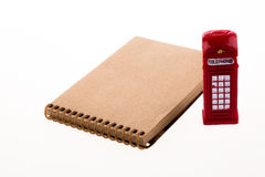 Telephone boot with notebook. Isolated telephone booth on a spiral note book on white background Stock Photos
