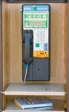 A telephone booth at fort nelson, canada. A pay-phone and phone book as seen in a small town in northern canada royalty free stock images