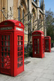 Telephone booths on a London street. Three red telephone booths on a London street Stock Photography