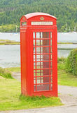 Telephone box by the sea. Stock Images