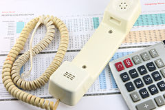 Telephone and calculator placed on Business graph. Royalty Free Stock Images