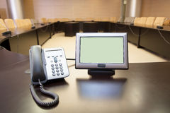 Telephone and computer display at conference table Royalty Free Stock Images