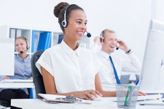 Telephone consultants at work. Happy telephone consultants with headphones at work Stock Photo
