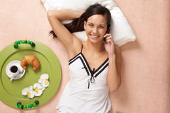 Telephone conversation. View from above of happy girl speaking on cellular phone on bed Stock Photo