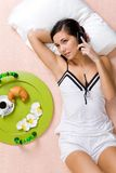 Telephone conversation. View from above of resting girl speaking on cellular phone on bed Royalty Free Stock Photo