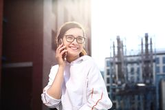 Happy, smiling young woman talking on the phone royalty free stock photography