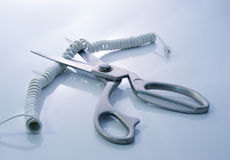 Telephone cord being cut by scissors Royalty Free Stock Photos