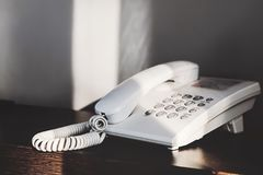 Telephone on the desk. Telephone with sunlight on the desk Royalty Free Stock Images