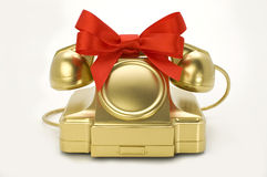 The telephone of gold colour with a red tape. Stock Photo