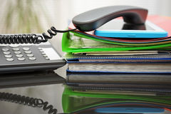 Telephone handset and tablet pc on top of the documentation in o Stock Image