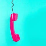 Telephone hanging on blue, vintage style photo Royalty Free Stock Photos