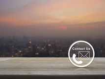 Contact us concept. Telephone and mail icon button on wooden table over blur of cityscape on warm light sundown, Contact us concept stock image