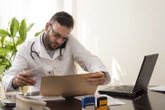 Telephone medical consultation. A doctor sitting at his desk. Talking on the phone by reviewing the patient`s medical records Telephone medical consultation Stock Image
