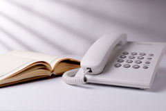 Telephone and open book. Landline dial up telephone and open note book or diary on a white table in sunlight with radiating shadows Stock Image